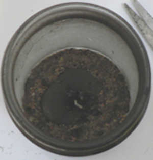 A different candle jar showing a well placed stone with the candle wax burned to nothing, leaving the wick tab